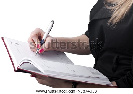 Young businesswoman writing notes to personal organizer.
