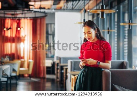 Young businesswoman. Young businesswoman owning restaurant wearing dark skirt and red shirt