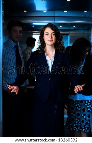 Young businesswomen arriving to office, using elevator.