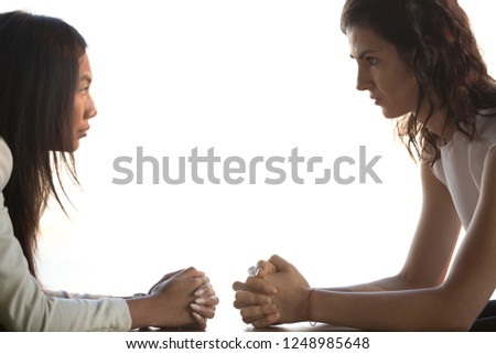 Young businesswomen sitting at desk with hands clenched together staring at each other unkindly, side view. Women struggling for leadership, having different opinions or discrimination at work concept