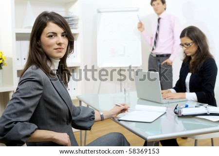Young businesswomen sitting at desk, writing notes. Businesswoman standing in background, drawing chart on whiteboard. Selective focus on woman in front.