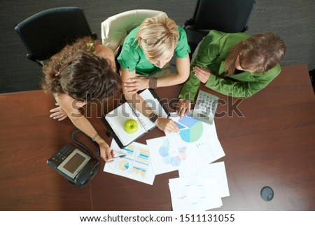 Young businesswomen sitting at table in meeting room, discussing finacial charts. Overhead shot. #1511131055
