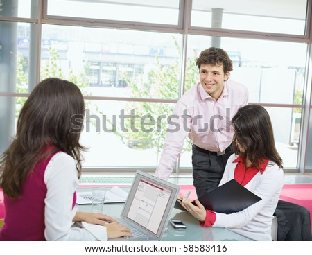 Young businesswomen working in office, using laptop computer, writing notes. Smiling businessman leaning on desk.