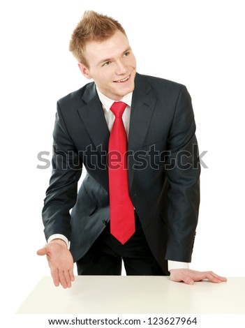 Young bussinesman standing near table, isolated on white background