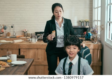 young busy asian employee mother rushing with daughter in morning going faster late for work and school. mom businesswoman take away toast breakfast hold backpack. child in uniform smiling walk leave