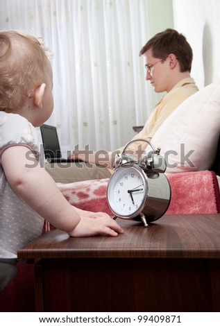 Young busy father with laptop ignoring his little daughter