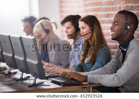 Young Call Center Team Talking With Customers