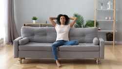 Young calm black woman relaxing sit on comfortable sofa in modern living room, lazy happy african woman girl resting on couch breathing fresh air enjoy peace of mind no stress free on couch at home