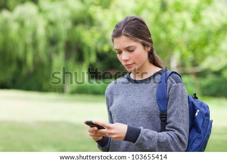 Young calm girl using her mobile phone to send a text while standing in a park