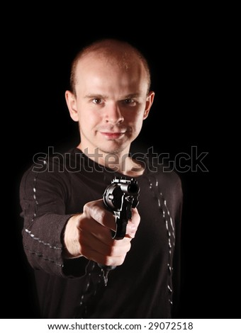 Young calm man with revolver gun on black background