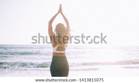 Young calm woman with hands up doing mountain pose for relieves chronic stress patterns enjoying morning training time on sea beach, concept of spirituality and recreation for minds and soul #1413815075