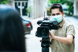 Young cameraman using a professional camcorder outdoor filming news while wearing mask mask prevent Covid-19 or coronavirus quarantine pandemic.