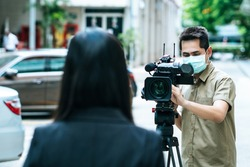 Young cameraman using a professional camcorder outdoor filming news while wearing mask prevent Covid-19 or coronavirus quarantine pandemic.