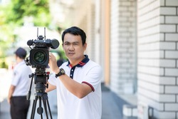 Young cameraman using a professional camcorder outdoor filming news with blur background.