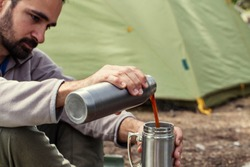 Young camper is sitting and prepairing his fresh hot coffee in front of his tent in the nature in a summer morning_2