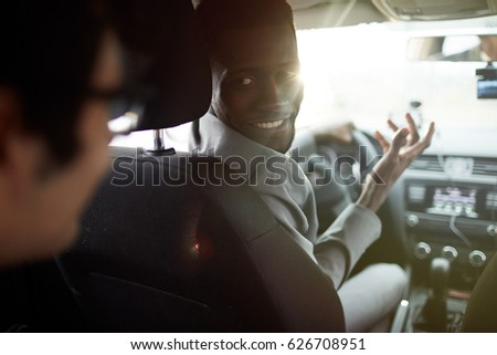 Young car driver asking businessman where to go