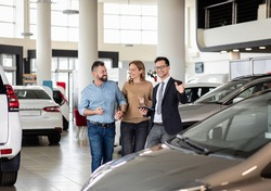 Young car salesman showing to mid-age couple new automobile at dealership salon.