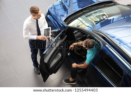 Young car salesman working with client in dealership Foto stock ©