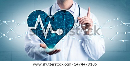 Young cardiologist holding a virtual heart displaying a pulse trace in the open palm of his right hand, while advising with raised index finger. Healthcare concept for cardiovascular health and AI.