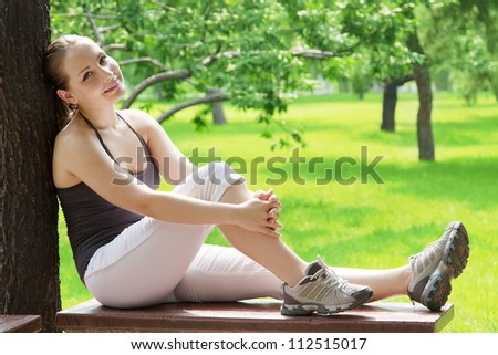 Young carefree blond woman sitting on bench in green park. Closeup portrait of teenager girl - stock photo