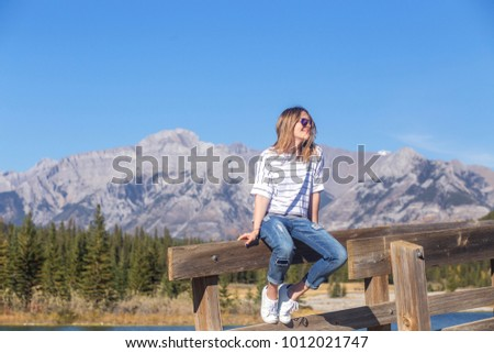 Young carefree smiling woman with windblown dark blond hair with highlights in casual outfit sitting on bridge rail looking away enjoying summer sunny windy day in Banff National Park, Alberta, Canada #1012021747