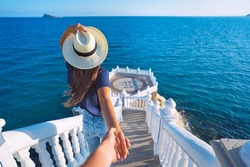 Young carefree tourist woman in white hat leading her boyfriend to the sea view. Follow me. Couple on summer holiday vacation. Traveling together. Balcon del Mediterraneo, Benidorm, Spain