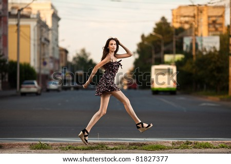 young carefree woman jumping at the street in city