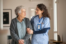 Young caregiver helping senior woman walking. Nurse assisting her old woman patient at nursing home. Senior woman with walking stick being helped by nurse at home.