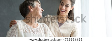Young caregiver in uniform hugging smiling elderly woman during a home visit
