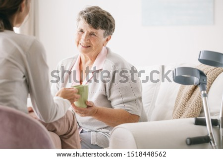 Young caregiver serving he tea to the older woman