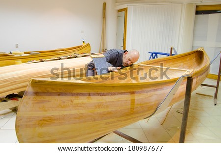 Young carpenter examining new canoe of his own design.