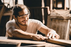 Young Carpenter happy working to making woodcraft furniture in wood workshop look professional high skill real people workman.