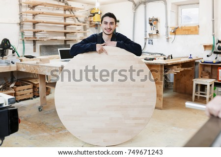 young carpenter in a joiner's workshop. The man holds a wooden round board for the text. Copyspace. young specialist, startup,