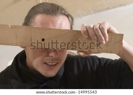 Young carpenter looking through hole of plank
