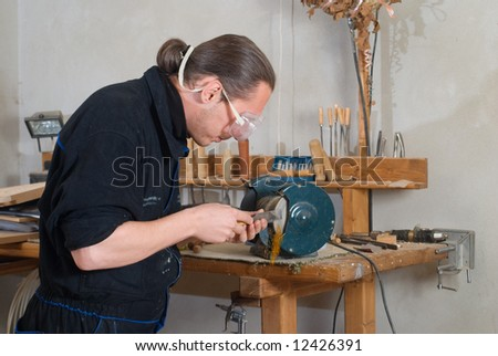 Young carpenter sharpen chisel on grinding machine, sparks fly