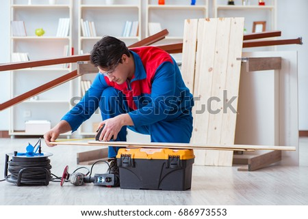 Young carpenter working with wooden planks #686973553