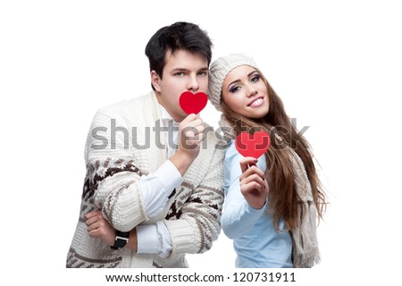 young casual caucasian brunette couple in winter clothing cover their mouths with red hearts and looking at camera with wide opened eyes