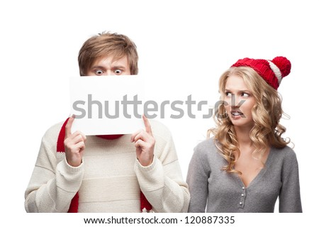 young casual caucasian couple in red scarf and hat holding sign with funny expressions