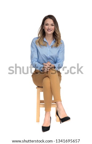 young casual dressed woman sitting on wooden chair with legs crossed and waiting for interview, full body picture #1341695657
