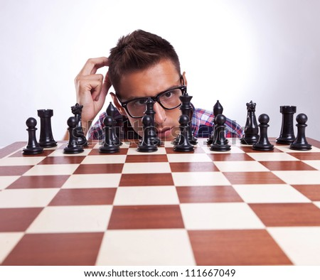 Young casual eyeglassed man in front of his first chess move. Over gray background.