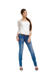 Young, casual, fashion, beautiful girl standing in studio in a T-shirt and jeans. Isolated on white background.