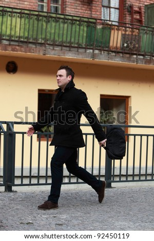 Young casual man in a hurry in a small cobbled city street.