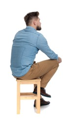 young casual man in denim shirt thinking and sitting isolated on white background, full body
