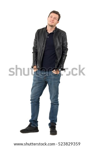 Young casual man in leather jacket and blue jeans with smirk smile tilting head. Full body length portrait isolated over white studio background.