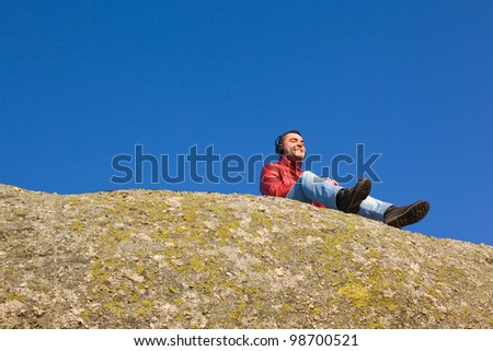 Young casual man listening to music outdoors