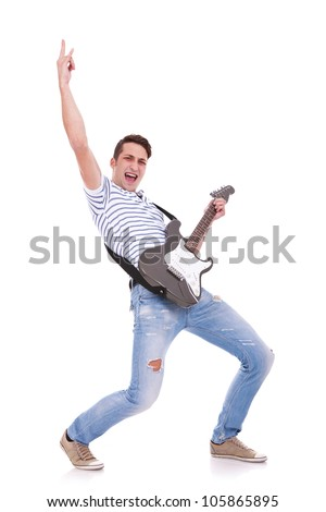 young casual man playing an electric guitar and making a rock and roll hand gesture while screaming