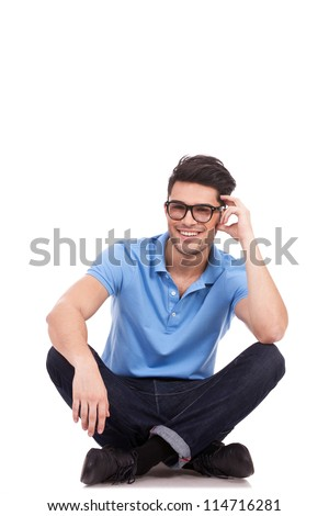 young casual man sitting with legs crossed and holding his head while smiling to the camera. isolated on white