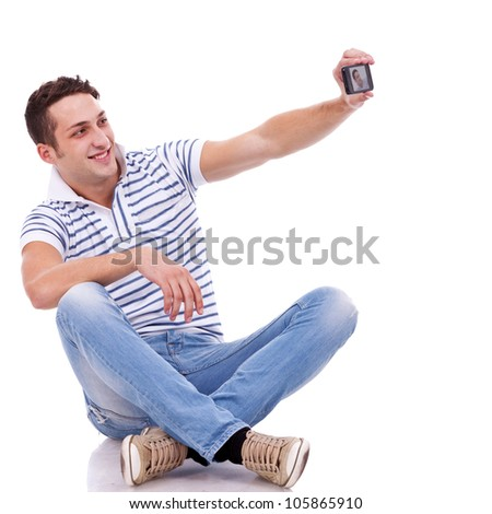 young casual man taking a picture of him self using a smart phone