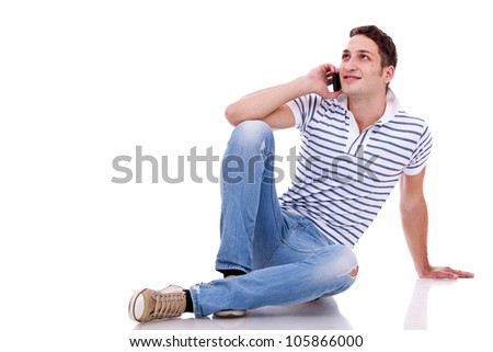 young casual man talking on the phone while lying on the floor