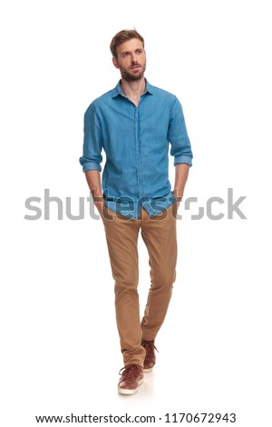 young casual man walking with hands in pockets on white background #1170672943